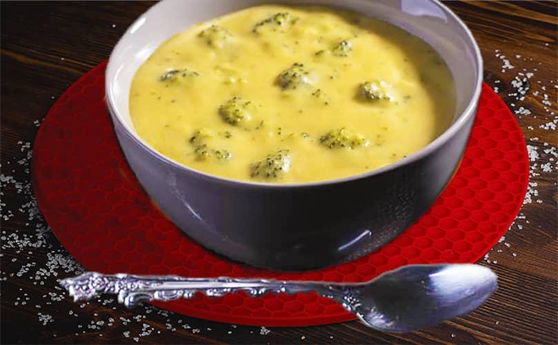 Broccoli cheddar soup on red trivets