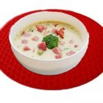 Creamy soup on red trivets